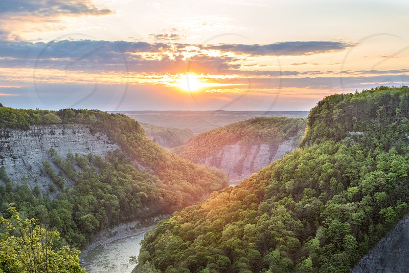 river between cliffs with green trees at sunset photo