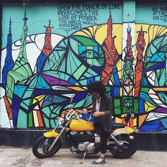 person on yellow motorcycle parked in front of mural photo