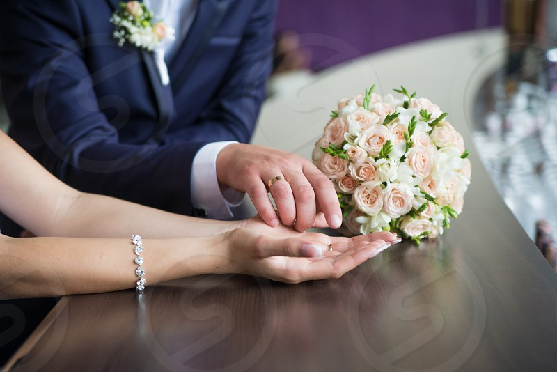 the couple holding hands wedding bouquet rings photo