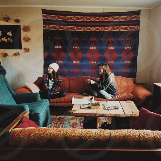 2 woman sitting on brown couch photo