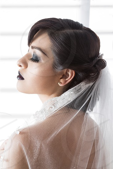 A gothic bride with her eyes closed next to a window photo