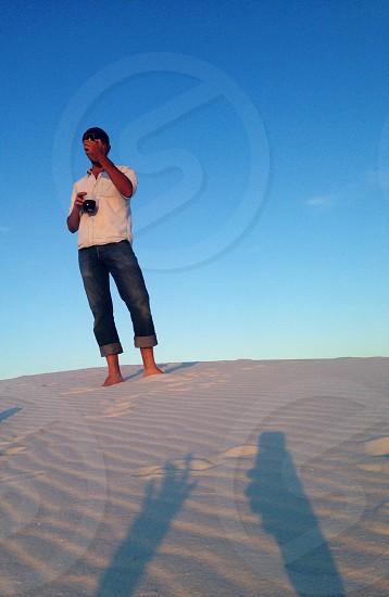 man in blue denim jeans standing in grey sand photo