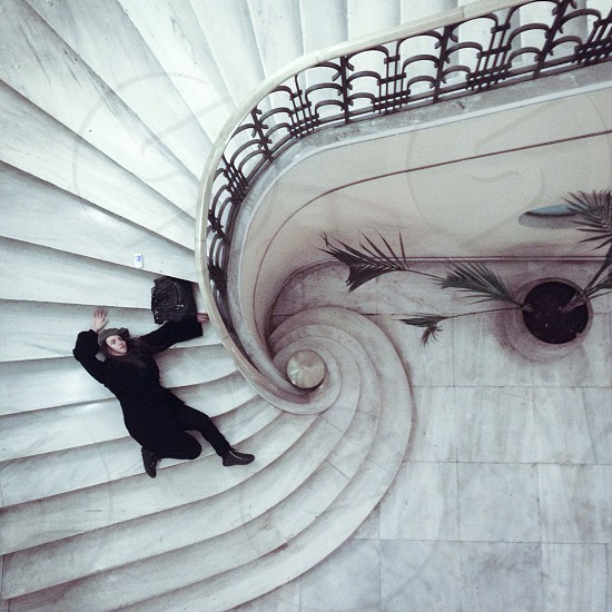woman in all black laying on white spiral staircase photo