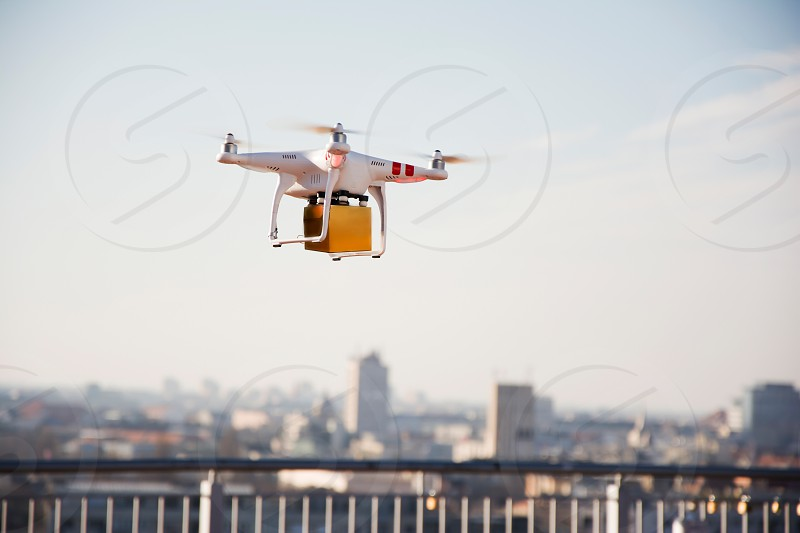 Drone flying over city caring a small package photo