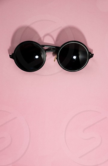 Top view flat lay vintage sunglasses on pastel pink background photo