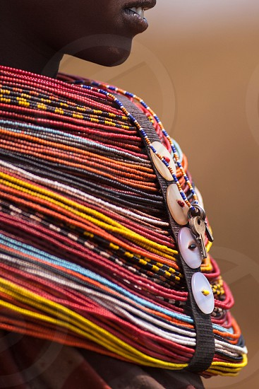 person wearing red yellow and white beaded tribal necklace photo