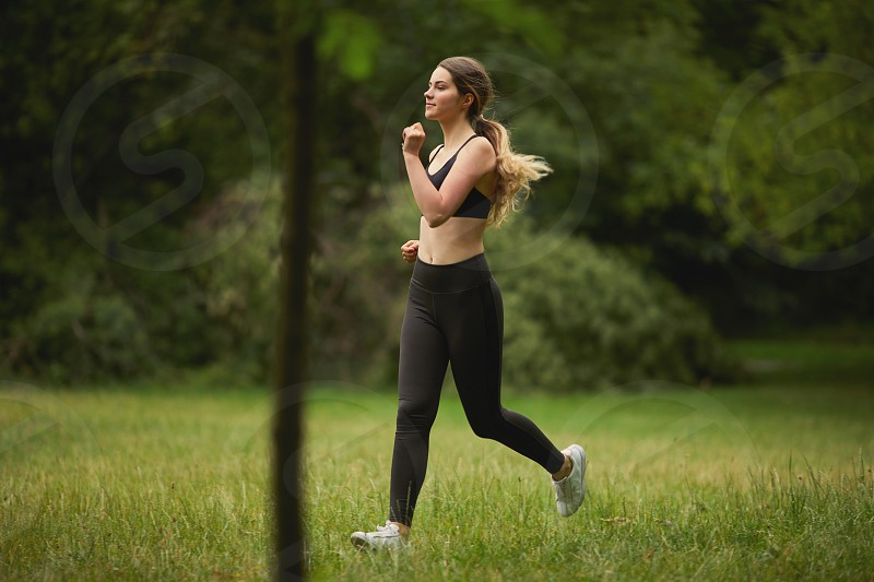 Fit pretty girl running on the park photo