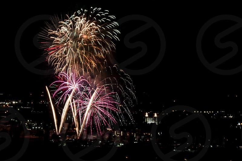 Fireworks display in Logan UT with city lights illuminated. photo