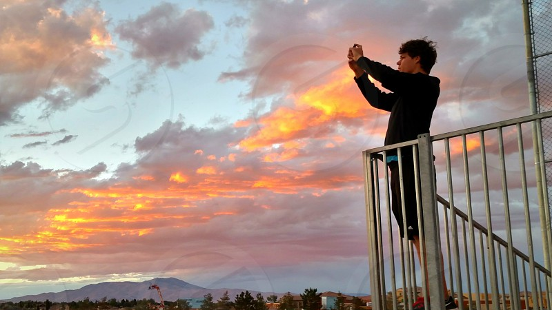 Young photographer on grandstand capturing beautiful sunset photo