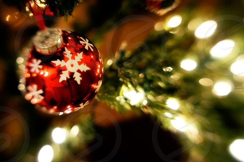 Red ball holiday ornament with snowflakes on a Christmas tree photo