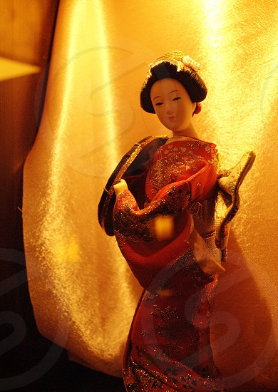 geisha doll in red and yellow floral kimono photo