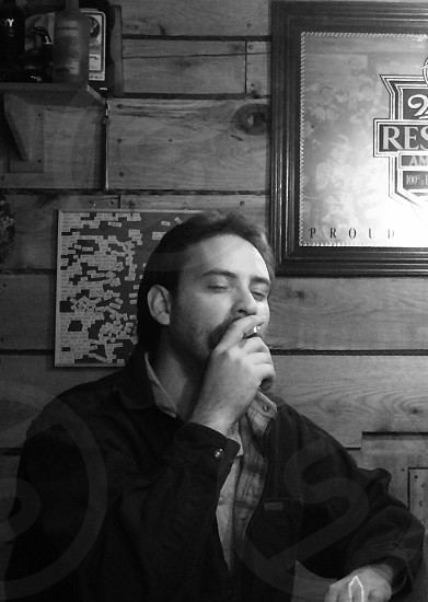 grayscale photography of man smoking cigarette photo