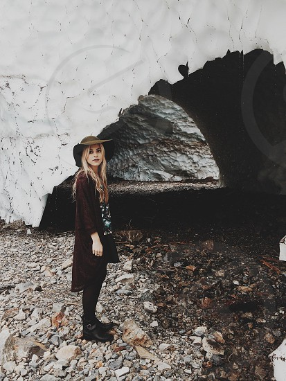 woman in black leather booties standing in front of cave photo