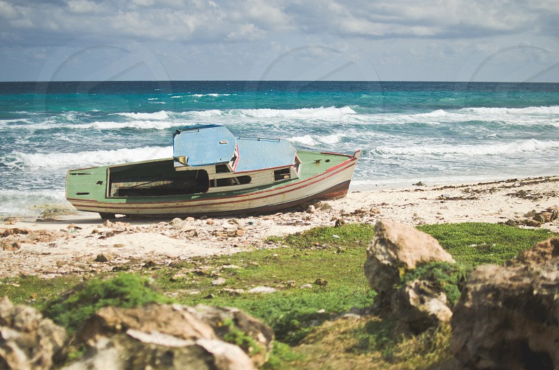Moored boat on a rocky beach by the Ocean. Isla Mujeres Mexico. photo