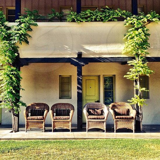 4 brown wooden rattan chairs in front of house photo