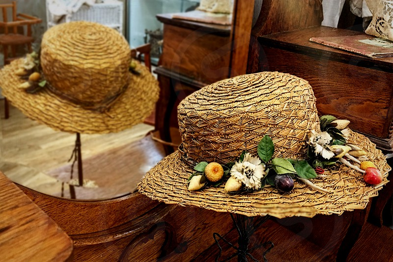 A pair of old-fashioned vintage straw hats sit of hat stands inside a store. photo