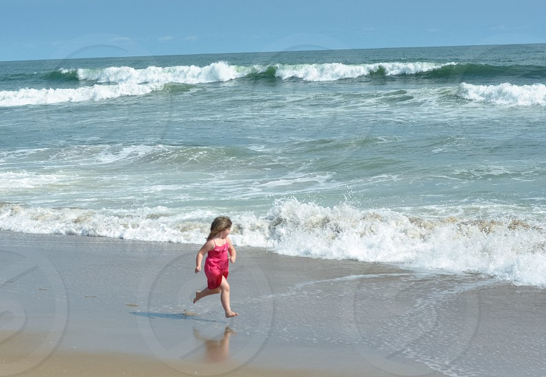 girl in pink running on seashore photo