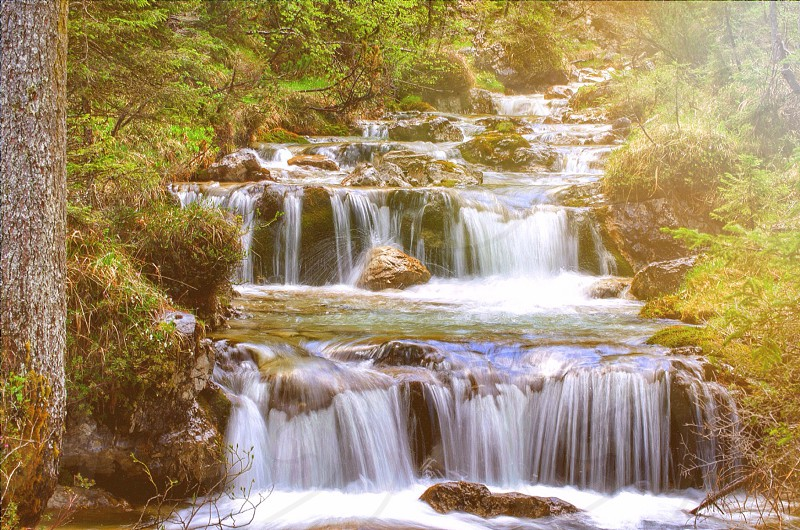 natural waterfall down multiple rock levels surrounded by green trees photo