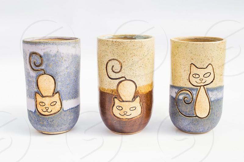 three ceramic stone jugs with white background photo