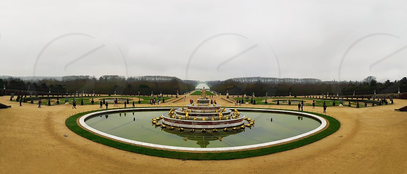 Panorama of Latona Fountain in the Garden of Versailles in France. World Heritage in a cold winter day bare trees and cloudy sky. photo
