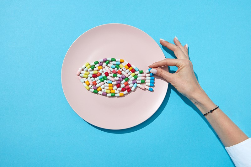 Many different pills and supplements as food on round white plate with woman's hand. Diet pills and supplements for dieting concept. Flat lay photo