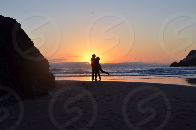 couple at the beach and sunrise silhouette  photo