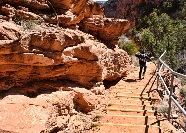 A boy runs down the steep stairway in a deep  rocky canyon photo