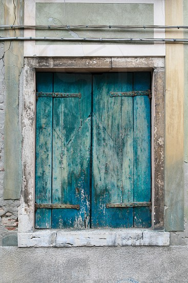 Old teal (blue green) closed wooden shutters on old building in Venice Italy photo