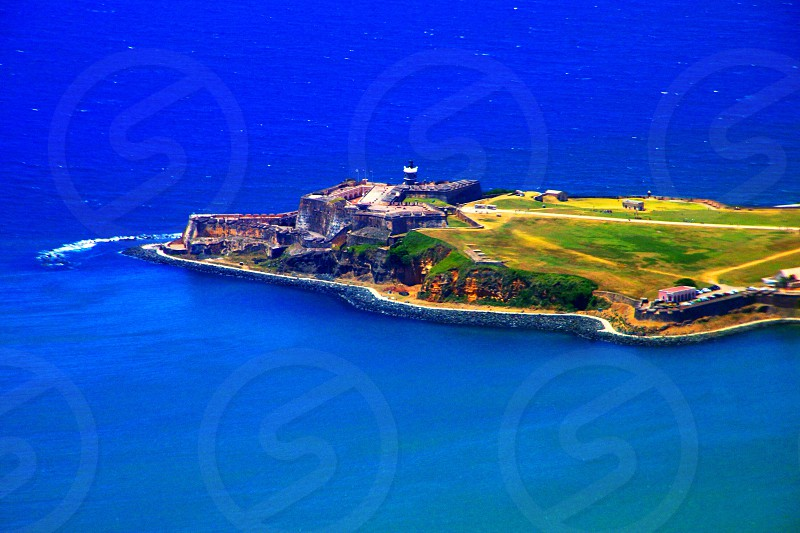 grassy island with large castle buildings photo