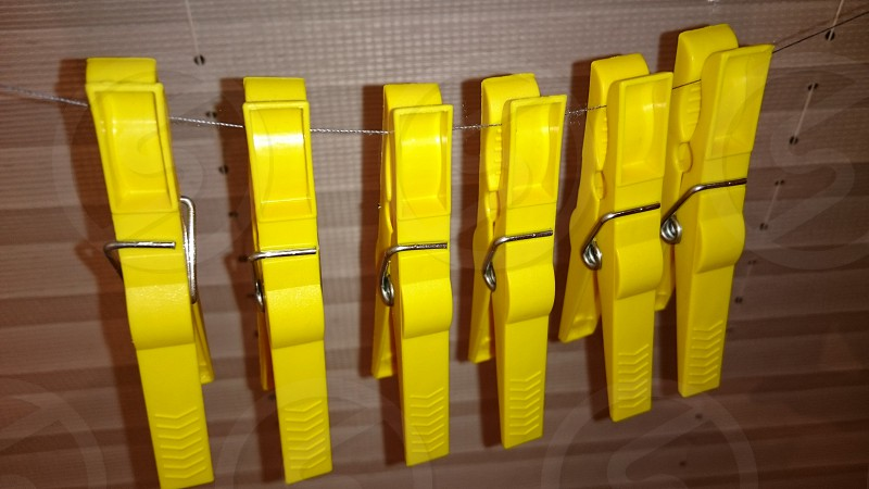 six yellow plastic clothes pins photo