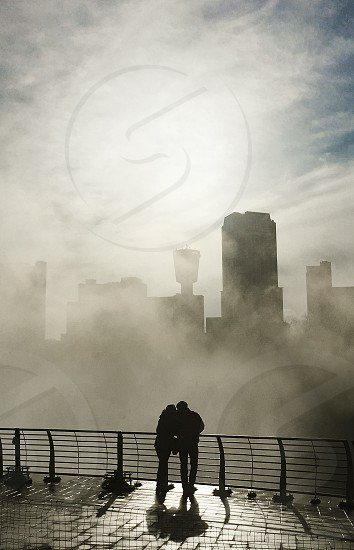 Young couple hugging in front of city and mist photo