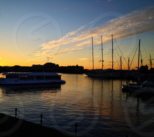 blue and yellow cloudy sky over white ferry and tall ships with sails down at sunset photo