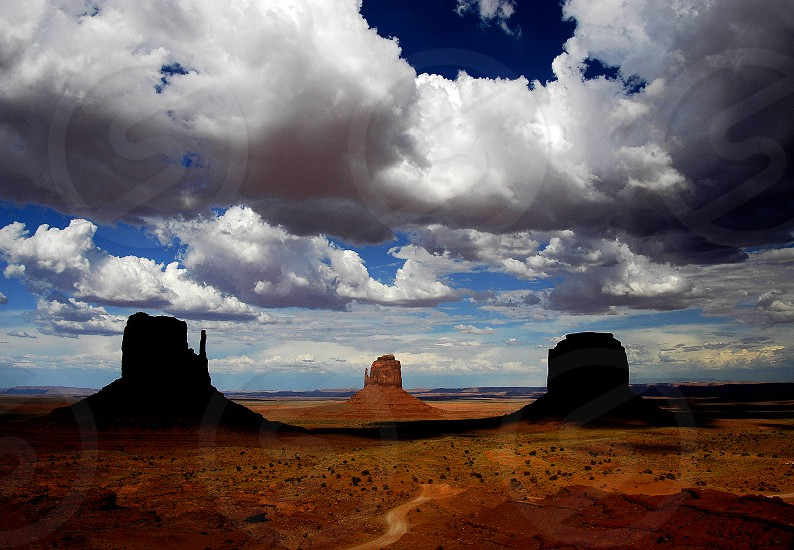 desert with 3 red rock formations blue sky with white puffy clouds casting shadows  photo