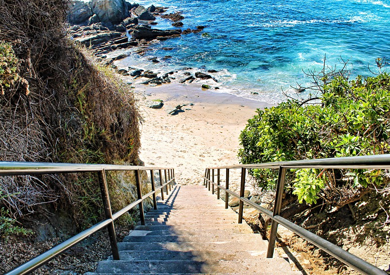 Looking down steps to a sandy beach and ocean photo