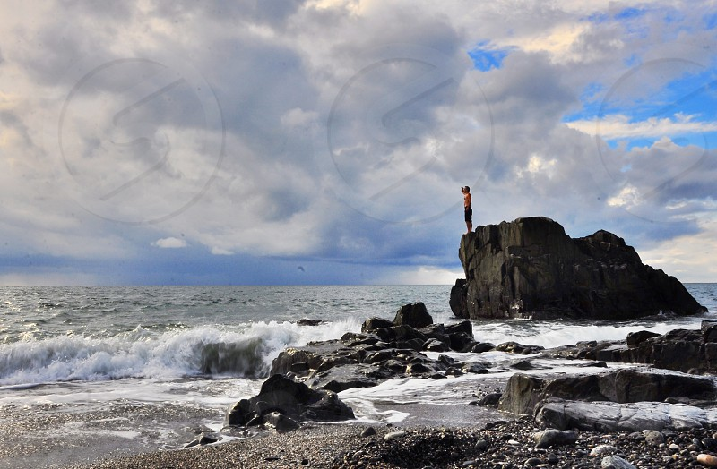 man standing at the edge of a gray rock photo