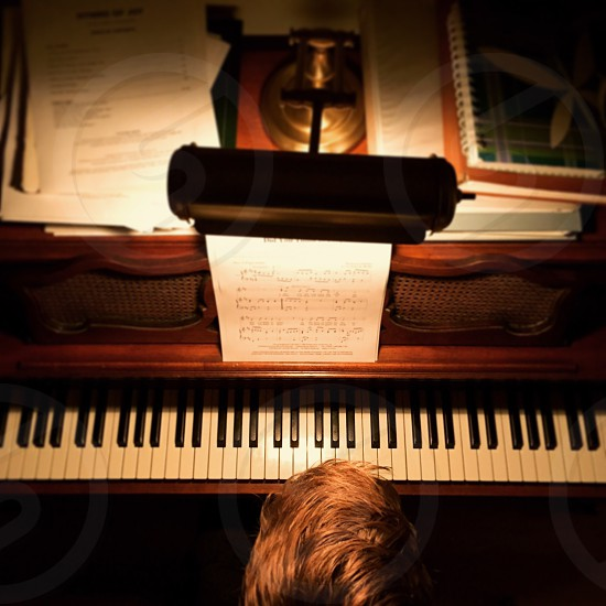 photo of man standing in front of piano photo