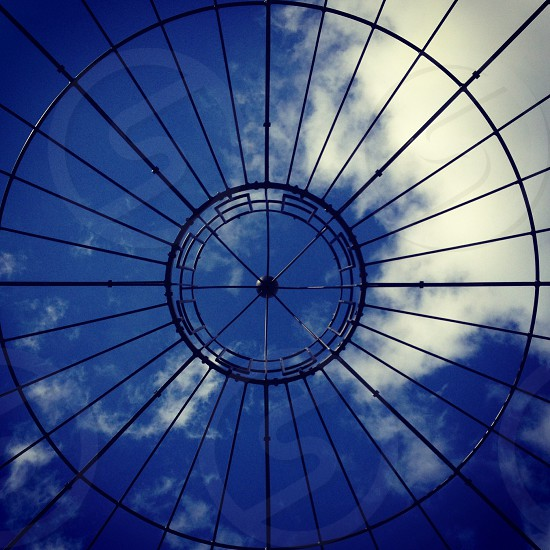 View looking up through a black metal window dome photo