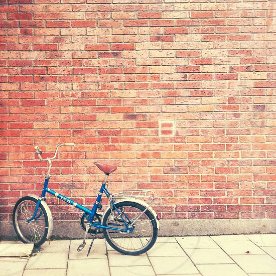 Vintage blue bike near a brick wall photo