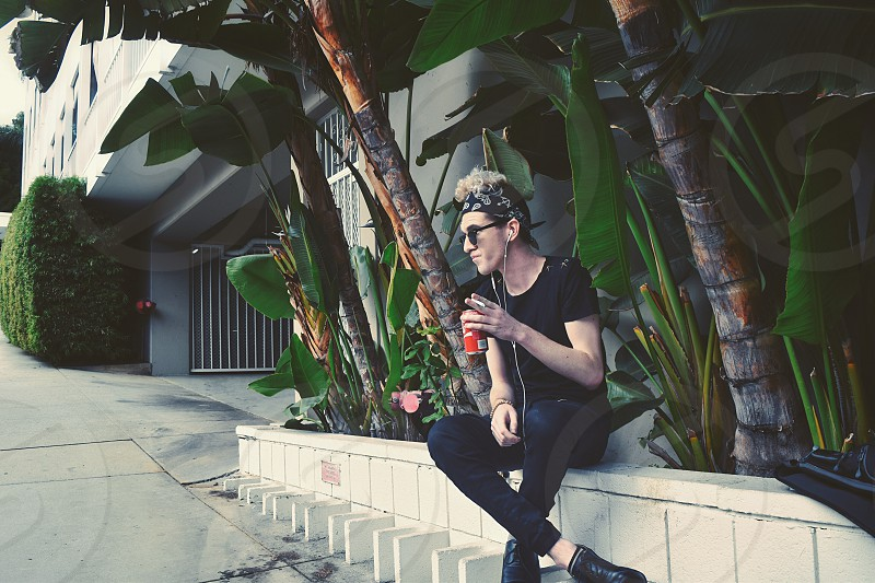 Young man black bandana curly hair blonde sunglasses Palm trees white wall soda staring summer smoking photo