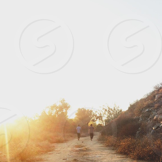 two people walking on a trail beside the hillside photo