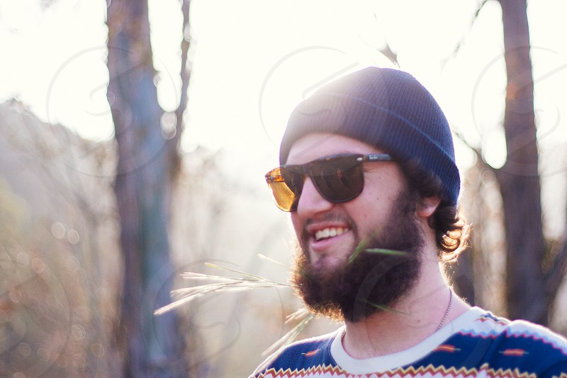 man in sunglasses and a blue beanie photo