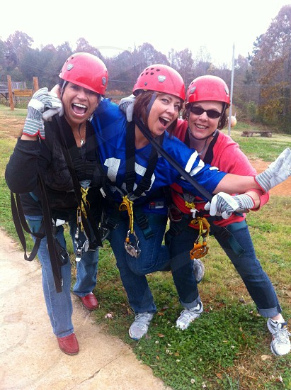 3 woman standing wtih safe harness on their body and all wearing a red helmet photo
