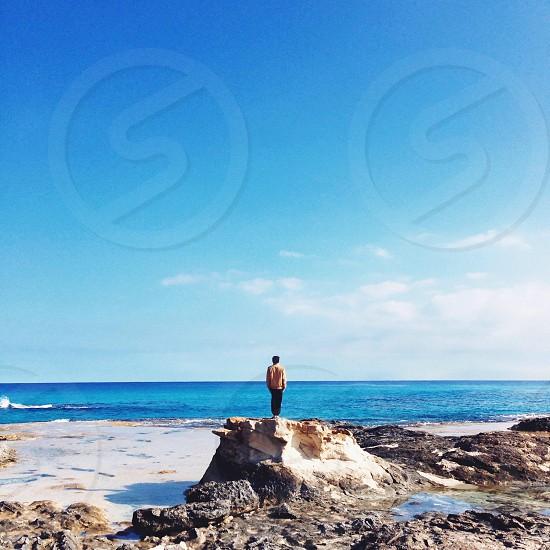 man standing on rocks at beach photo