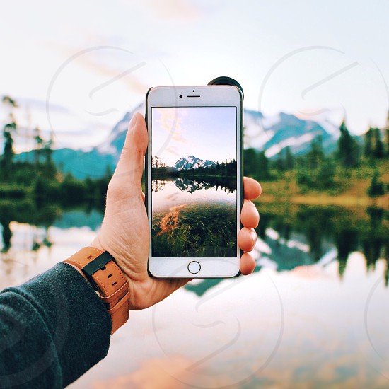 person holding silver iphone taking photo of snow covered mountain during daytime photo