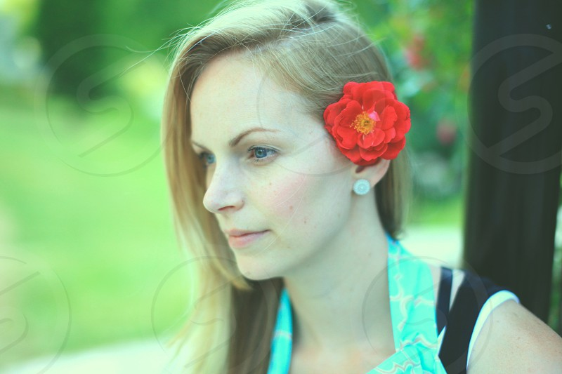 woman in blue halter-strap top with red petaled flower on her ear photo