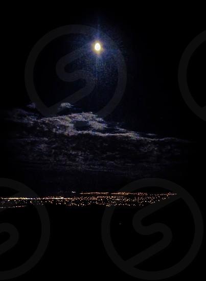 Moonlight shines over Utah city lights exposing clouds. Summer 2014 photo