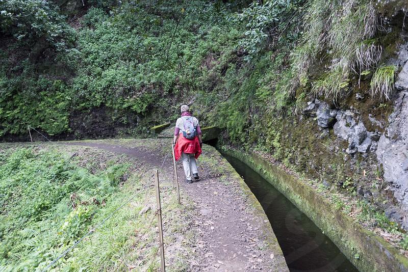 woman walking on levade walking track  on the portugal island of Madeira this is Lamaceiros Ribeira da Janala photo