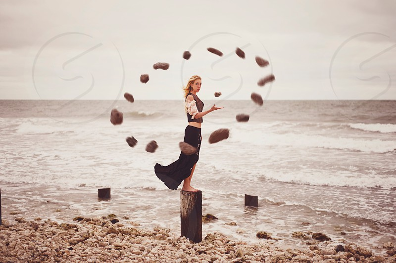 woman in black vest and black skirt standing on brown wooden post on beach shore near rocks forming circle on mid air during daytime photo