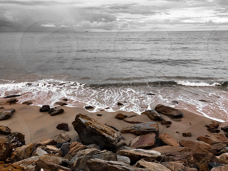 rock ocean sea wave beach sky nature shore coast landscape water stone seascape sand bay background pebble overcast tide orange shoreline sandy rough tranquil cloud storm rocky outdoor cloudy brown monotone bw black and white sepia color splash Thailand south photo