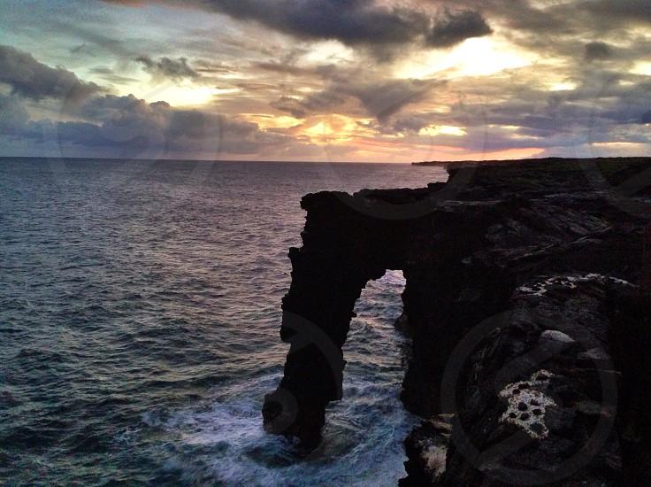 black rock formation near ocean photo